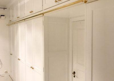 Platsbyggd garderob med stång för tillhörande stege.