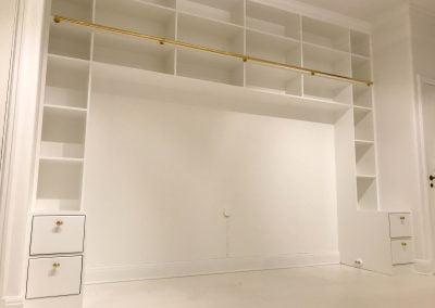 Platsbyggda lådor och hyllor med stång för tillhörande stege.